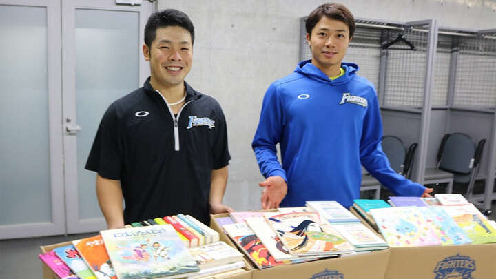 札幌ドームで来場者から回収した書籍と近藤選手、中島選手 ©️H.N.F.